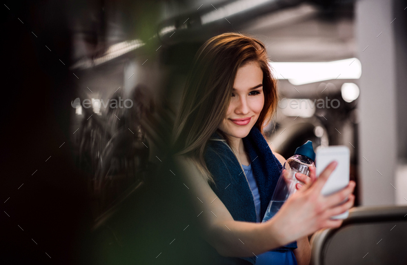 A portrait of young girl or woman with smartphone in a gym, taking selfie. - Stock Photo - Images