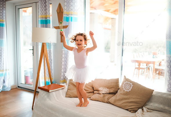 A small girl with a princess dress at home, holding a toy sword and jumping. - Stock Photo - Images