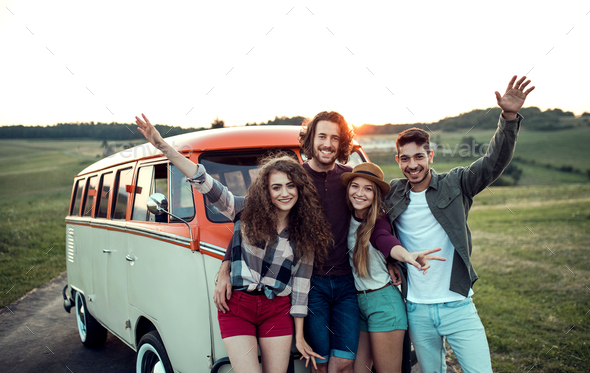 A group of young friends on a roadtrip through countryside, standing by a minivan. - Stock Photo - Images