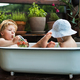 Small children with a drink sitting in bath outdoors in garden in summer. - PhotoDune Item for Sale