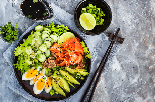 Salmon poke bowl served with avocado, eggs, cucumber and greens - Stock Photo - Images