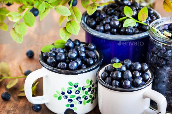 Fresh ripe bluberries (bilberries) in enamel mugs - Stock Photo - Images