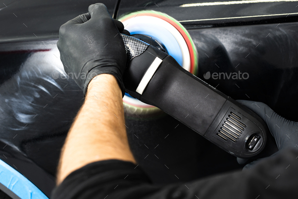 Buffing and polishing car. Car detailing. Man holds a polisher in the hand and polishes the car - Stock Photo - Images