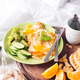 Breakfast eggs on a white plate with half avocado, cucumbers on a wooden plate on bed - PhotoDune Item for Sale