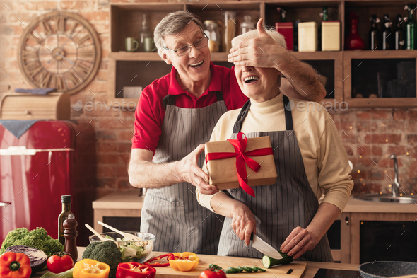 Senior woman receiving gift from her loving husband in kitchen - Stock Photo - Images