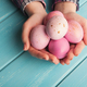 Woman holding pink colored easter eggs on blue table - PhotoDune Item for Sale