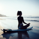 Woman surfer meditation sit on surfboard on beach - PhotoDune Item for Sale