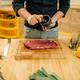 Male person sprinkles raw meat with seasonings - PhotoDune Item for Sale