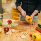 Chef with knife cuts yellow pepper on wooden board - PhotoDune Item for Sale