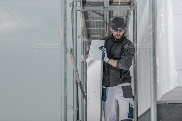 Worker with Piece of Insulation - Stock Photo - Images