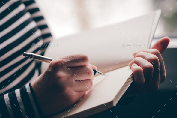 Woman writing diary by the window - Stock Photo - Images