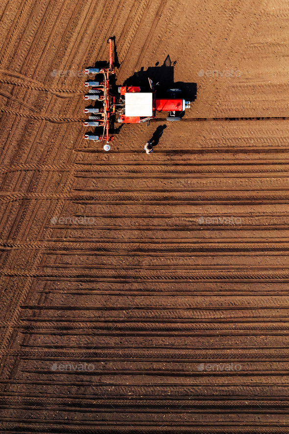 Aerial view of farmer and tractor with crop seeder - Stock Photo - Images