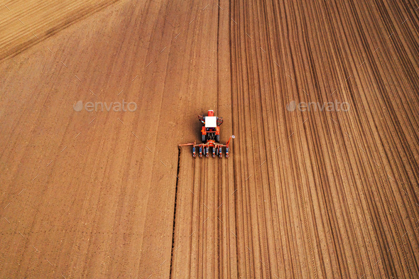 Drone photography of tractor with seeder working in field - Stock Photo - Images