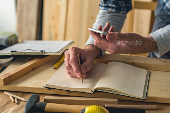 Carpenter is writing project notes while using smartphone - Stock Photo - Images