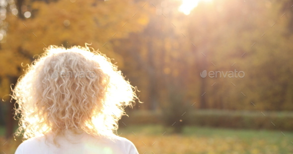 Beautiful blonde woman touching curly hair, walking in autumn park - Stock Photo - Images