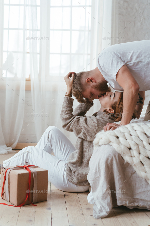 The guy on the bed kisses a girl who sits on the floor - Stock Photo - Images