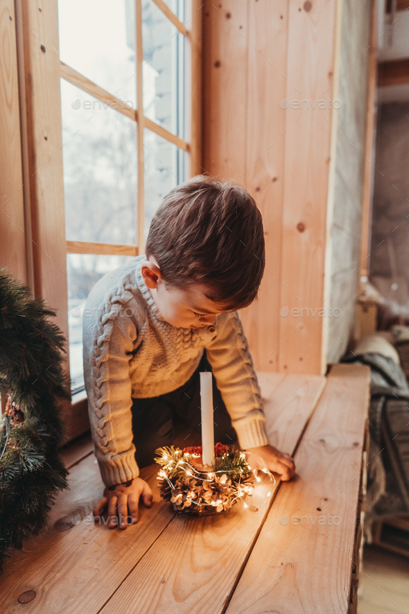 Little boy playing with a candle. Child is sitting on windowsill - Stock Photo - Images