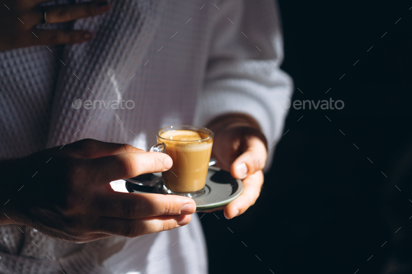 A man in a bathrobe is holding a small mug of coffee - Stock Photo - Images
