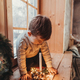 Little boy playing with a candle. Child is sitting on windowsill - PhotoDune Item for Sale