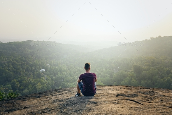 Man resting on top of rock - Stock Photo - Images
