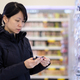 Beautiful Asian woman choosing personal care product in supermarket - PhotoDune Item for Sale