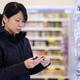 Beautiful Asian woman choosing personal care product in supermarket - PhotoDune Item for Sale