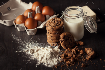 Chocolate cookies on rustic wooden table with bottle of milk, white flour, fresh eggs,butter and