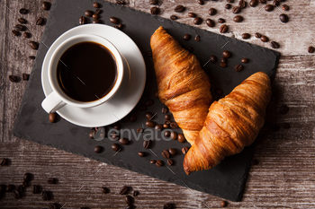 Croissant and cup of hot coffee on dark wooden table