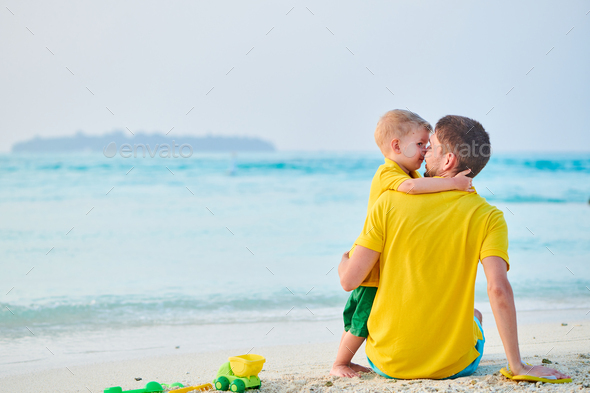 Toddler boy on beach with father - Stock Photo - Images