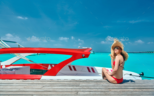 Woman in bikini sitting on jetty with boat - Stock Photo - Images