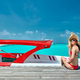 Woman in bikini sitting on jetty with boat - PhotoDune Item for Sale