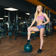 Young athletic woman in mini shorts holding one leg on a ball in the gym - PhotoDune Item for Sale