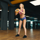 Image of young attractive female in mini shorts doing exercise on gym background - PhotoDune Item for Sale