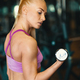 Young woman in pink top and mini shorts doing exercise with dumbbells while training arms at the gym - PhotoDune Item for Sale