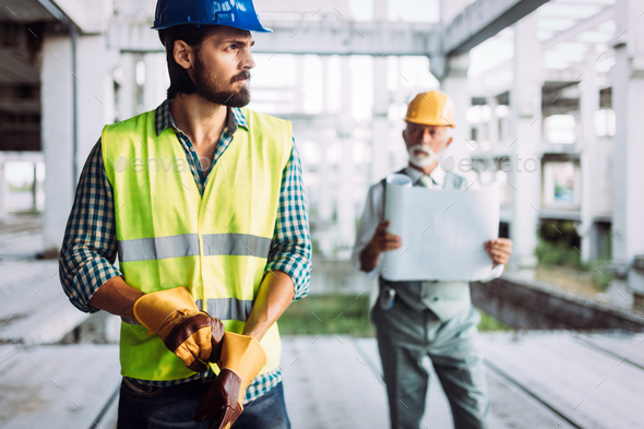 Engineer, foreman and worker discussing in building construction site - Stock Photo - Images