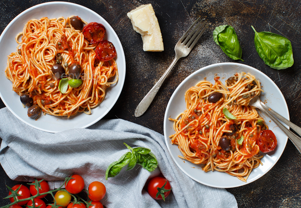 Pasta alla puttanesca - Spaghetti with tomato sauce olives and capers - Stock Photo - Images