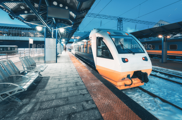 High speed train on the railway station at night - Stock Photo - Images