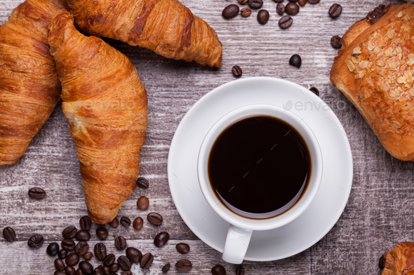 Cup of hot coffee and freshly baked croissants on dark wooden table - Stock Photo - Images