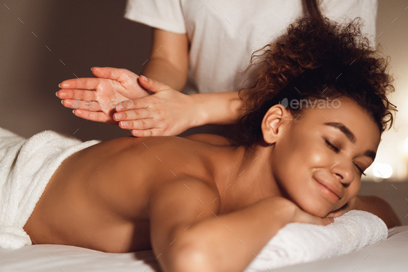 African-american woman getting spa treatment in healthy center - Stock Photo - Images