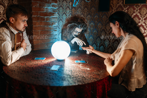 Foreteller guessing by hand over a crystal ball - Stock Photo - Images