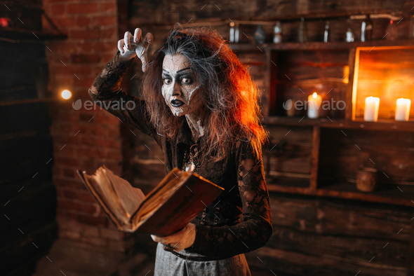 Witch holds spellbook, dark powers of witchcraft - Stock Photo - Images