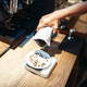 Barista hand pours coffee beans into the plate - PhotoDune Item for Sale