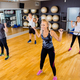 Focused team doing squat exercises with weights at fitness gym - PhotoDune Item for Sale