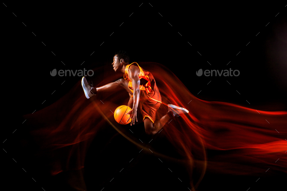 Young basketball player against dark background - Stock Photo - Images