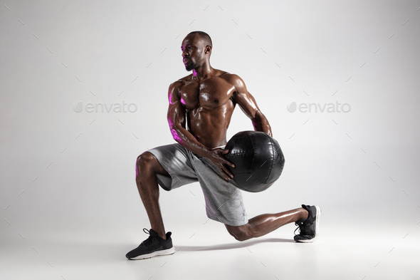 Young african-american bodybuilder training over grey background - Stock Photo - Images