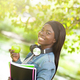 Smiling african female student holding an apple. - PhotoDune Item for Sale