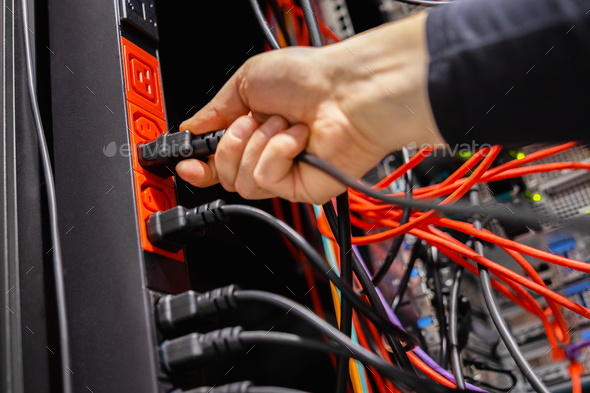 Male Technician insert Power Cable in Outlet in Datacenter - Stock Photo - Images