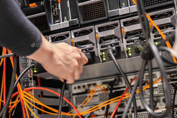 Male Technician Plugging Power Cable In Panel At Datacenter - Stock Photo - Images