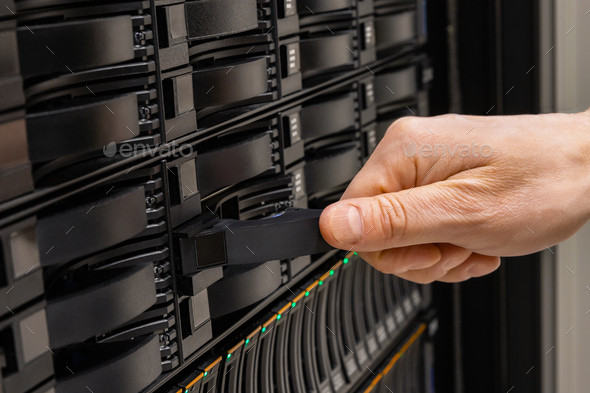 Male IT Engineer Replacing SAN Server Drive From Rack - Stock Photo - Images