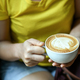 Women's hand holding a cup of latte coffee leaf shaped. - PhotoDune Item for Sale